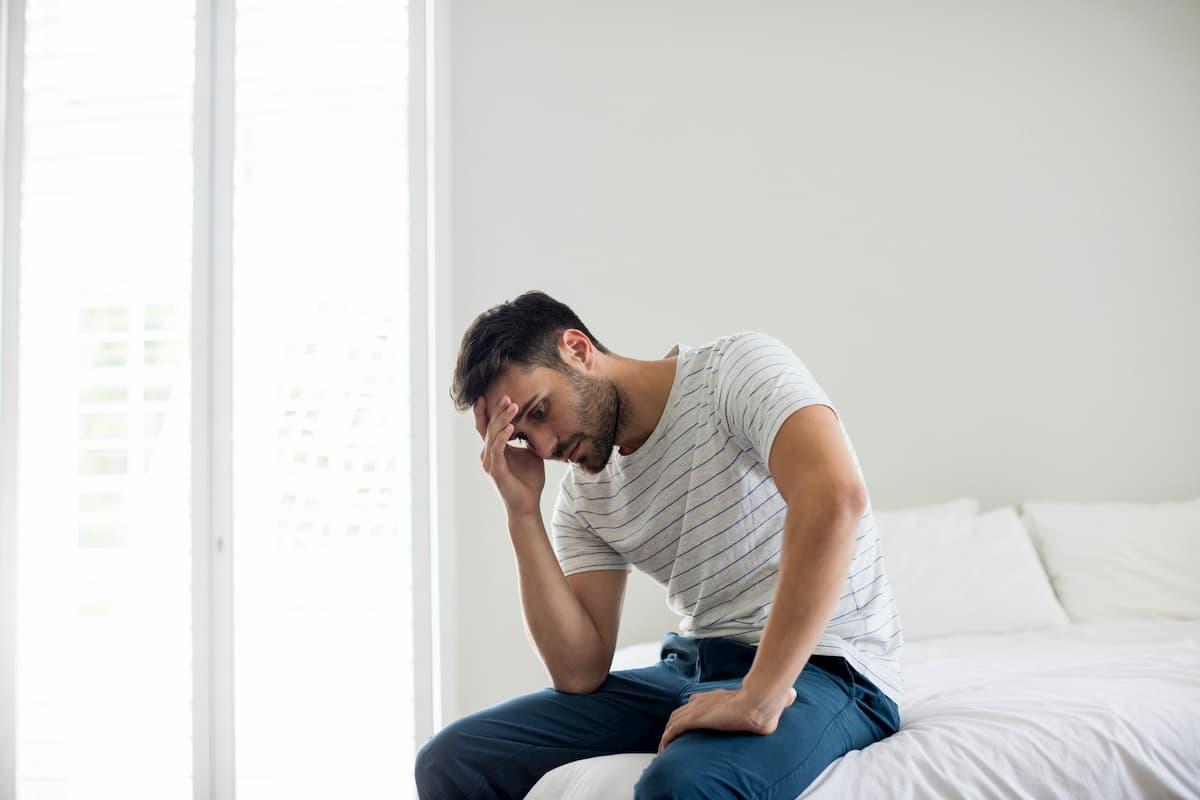 寝室で頭を抱える男性